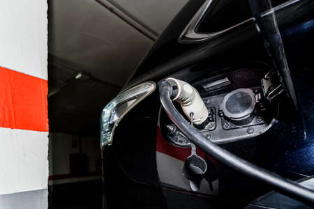 A car recharges its electric batteries inside a private garage with its own charging station, detail of the connected plug.