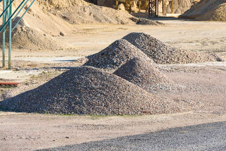 Velt conveyors and a piles of rubble in gravel quarry, crushed sand in different sizes. Stock fotó