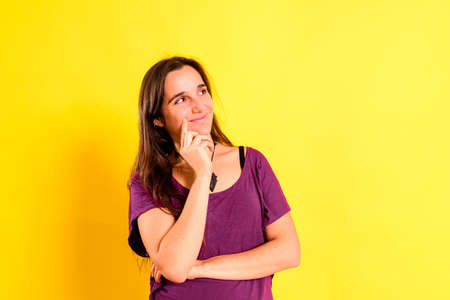 Normal young woman with relaxing meditative gesture dressed casual, isolated on studio background.
