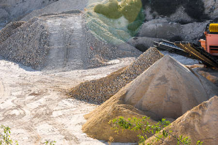 Velt conveyors and a piles of rubble in gravel quarry, crushed sand in different sizes.