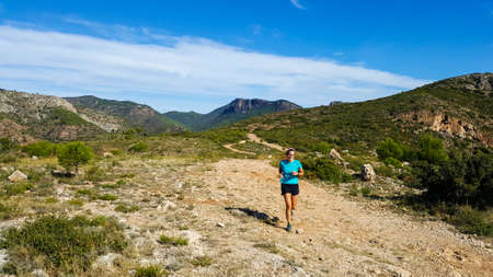 Real-looking middle-aged woman runs down a mountain trail. Stock fotó