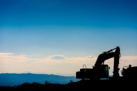 Backlit silhouette of an excavator on top of a hill with unfocused sky background.