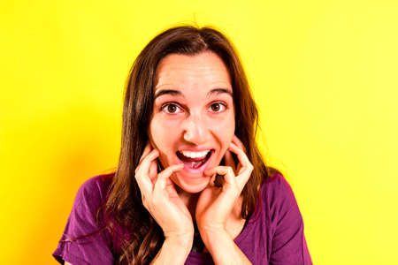 Portrait of a young woman with scared and shocked expression with surprise, fear and excited face, on isolated background.