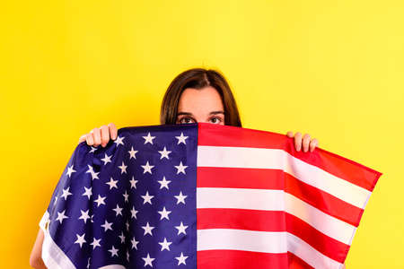 young scared latin woman covers herself with an american flag in fear of deportations, isolated on yellow background.