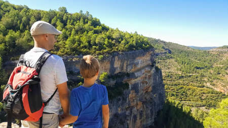 A father and son admire the mountainous landscape as they rest from their hike.