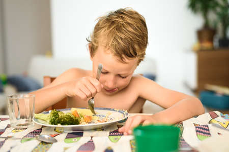 Child eats healthy broccoli at noon with summer fork at home with nice smile