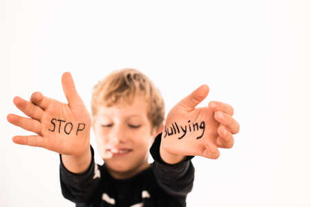 Stop Bullying written on the palms of a child in a black t-shirt isolated on a black background.