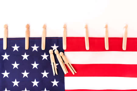 American flag fastened with clothespins on a white background, copy space for text.