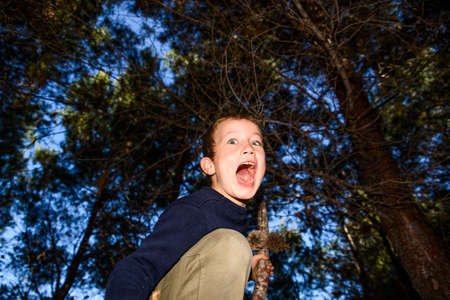 Scared child screams in fear, lost in a dark forest.