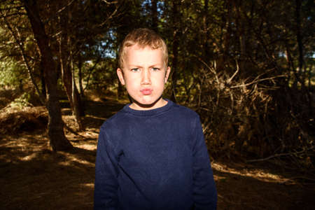 Young boy in a dark forest putting up duck faces to spoil a preadolescent photo