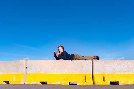 A child play on some construction barriers running into danger, isolated blue background.