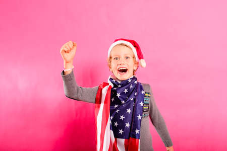 Blond boy with santa hat, American flag and raised fist in victory sign.