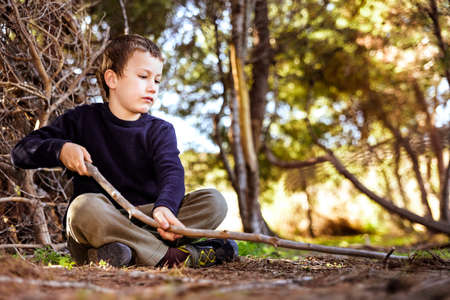 A child sitting on the ground in a forest uses a stick to draw on the ground and experience nature.