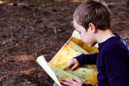 Boy trying to read an old travel map, lost in a forest, in search of adventure. Banque d'images