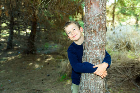 Child hugging a tree in a dark forest, taking care of the planet.