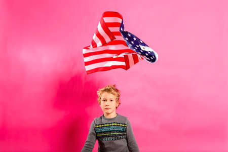 Blond boy under a floating American flag, isolated on a pink background.