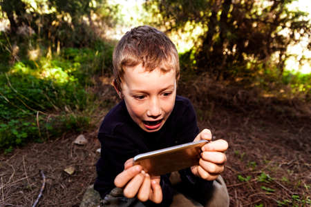 A boy with an expression of great amusement has a great time watching videos on his smartphone while in a forest. Banque d'images