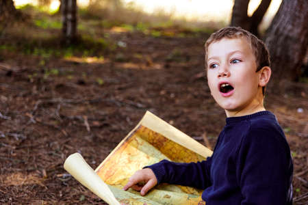 Child with astonished expression to find the location on an old map of a treasure in a forest. Banque d'images