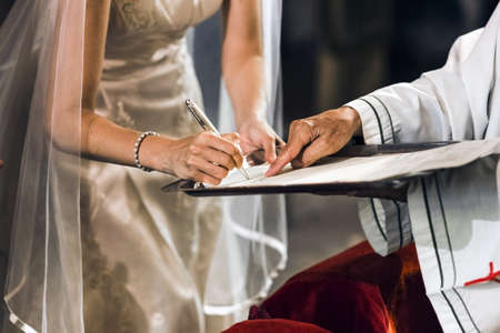 A bride signs her wedding contract on the altar of a church with a priest. Banque d'images