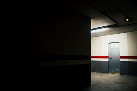 A mysterious metal door in the dark interior of a lighted garage.