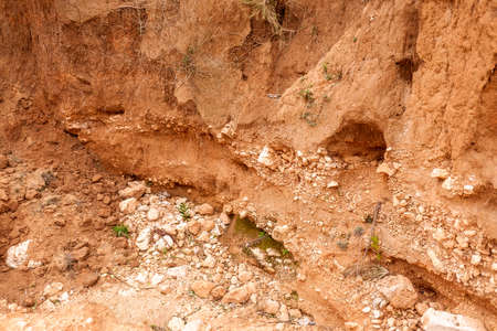 Frontal detail of different strata and layers of rock and earth on a slope.