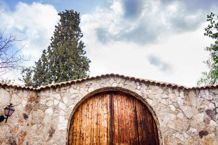 Beautiful wooden door with a round high part, in a stone wall of a rural property.