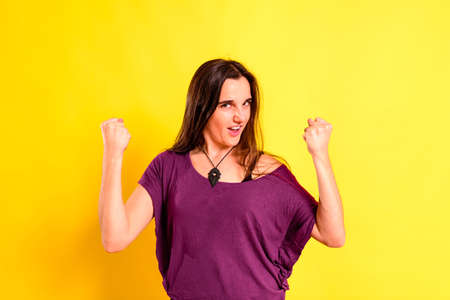 Young woman with proud attitude for a triumph and her achievements made by herself, isolated on yellow background.