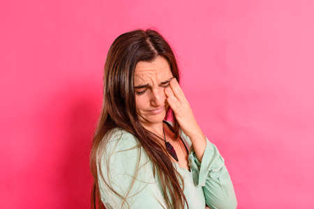 Young 25 year old student girl with headache and body discomfort, isolated on colored background.