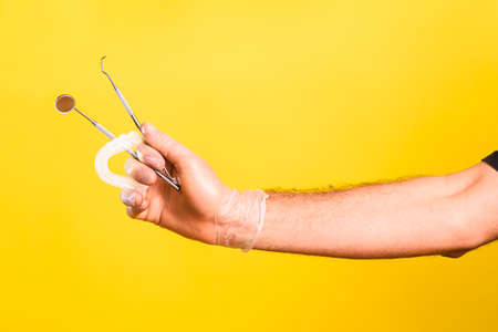 Dentist hand shows and holds mirror, scaler and a dental aligner, isolated on yellow background.