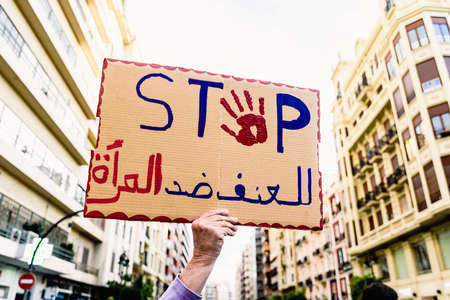 Banner with the word Stop, message to the Arab world, during a protest.