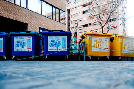 Valencia, Spain - March 25, 2021: Containers of organic, paper and plastic garbage for recycling on a city street. 新闻类图片