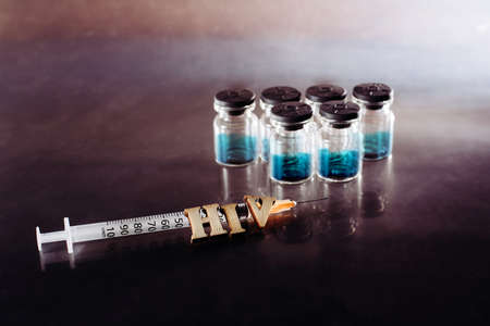 New AIDS treatment, vaccination with syringe with new vaccine, letters HIV on medical background.