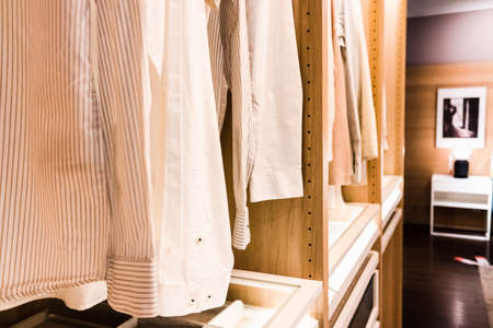 Clean men's shirts hang in a closet in a private dressing room.