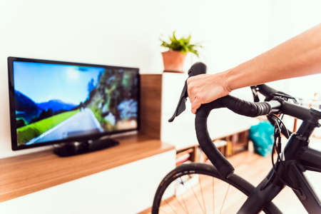 Woman exercises indoors using her bike for a virtual race. Imagens