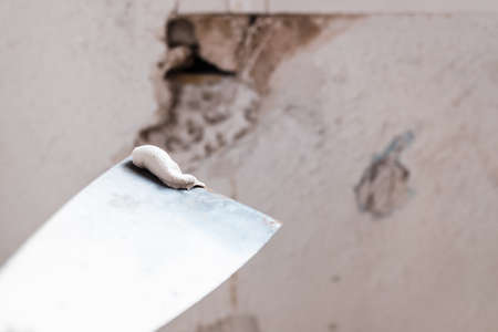 Applying white cement to a crack in a wall with a putty knife. 免版税图像 - 167076208