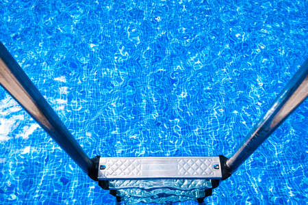 A pool with a metal ladder to access it and bathe in summer. Imagens