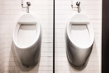 Two wall urinals in public toilets. Imagens