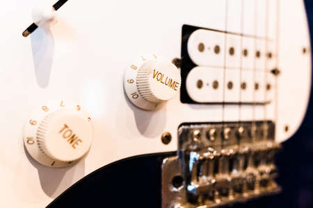 Detail of an electric guitar with its volume buttons, hanging as a decoration.