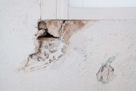 Detail of the damage to a wall inside a house caused by humidity.