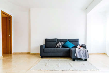 Simple sofa in a spacious room with no decoration, minimalist white walls with great lighting. Imagens