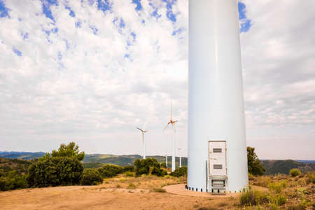 Field of wind turbines, with the large tower of one in the foreground. Imagens