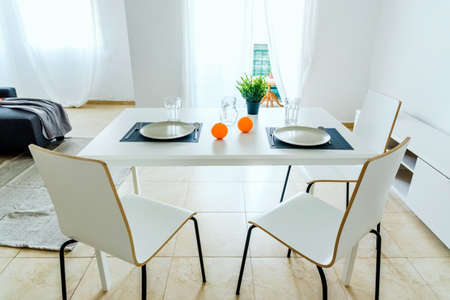 Simple white table in a very simple and bright minimalist living room. 免版税图像 - 167255393