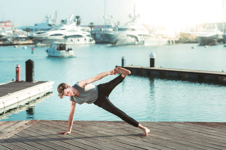 Trikonasana, yoga posture executed by a young red-haired athlete outdoors in a city near the sea, copy space. 免版税图像