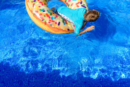 6-year-old boy bathing in a transparent pool playing with a large donut-shaped float. Imagens