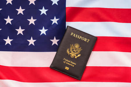 American passport next to a patriotic flag.