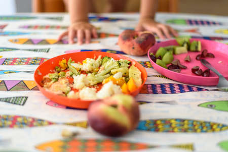 Detail of a plate with vegetables for children on a table.