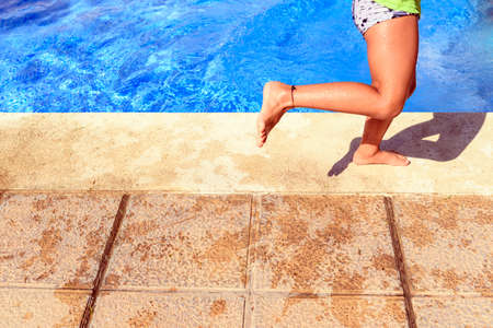 Child enjoying the last days of summer in a pool in full sun.