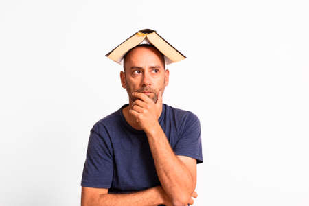 Funny man with an open book on his head thinks and has ideas.