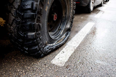 Valencia, Spain - April 15, 2021: Flat tire of an off-road car parked on a street. 新闻类图片