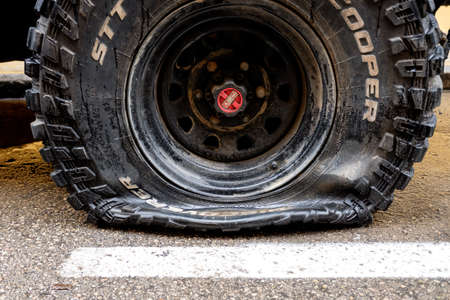 Valencia, Spain - April 15, 2021: Wheel with a puncture in a 4x4 vehicle, parked on a city street.